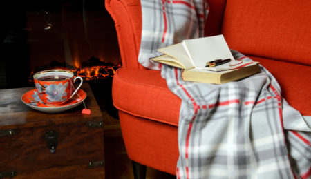 Blanket and tea cup by the fireplace