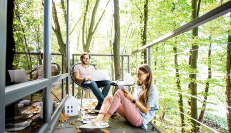 Creative couple of architects working outdoors at the forest house