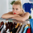Thoughtful sad beautiful blonde woman standing near wardrobe rac