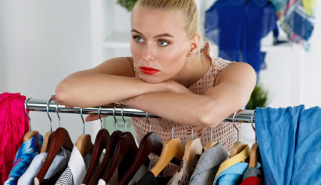 Thoughtful sad beautiful blonde woman standing near wardrobe rac