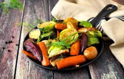 Skillet of roasted vegetables against rustic wood