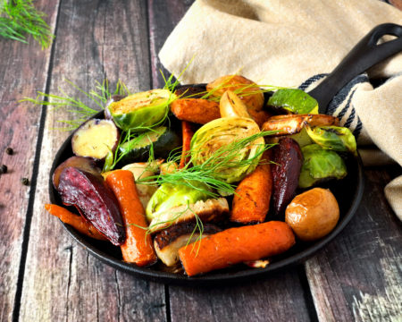 Skillet of roasted vegetables against rustic wood