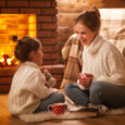 family mother and child drinking tea and laughing on winter evening by fireplace