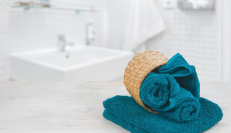 Green-blue folded towels in wicker basket over defocused bathroom