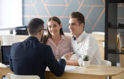 Insurance agent consulting millennial couple in office