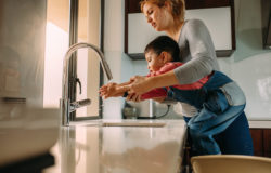 Son washing hands with mother in the sink
