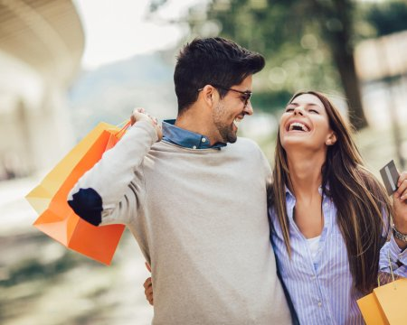Young couple with shopping bags and credit card in the city