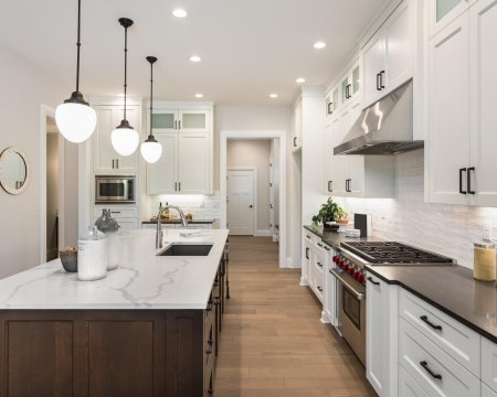 beautiful kitchen in new luxury home with island, pendant lights, and glass fronted cabinets