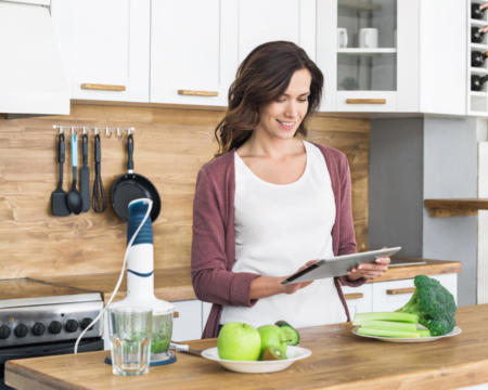 Woman preparing food following recipe using digital tablet