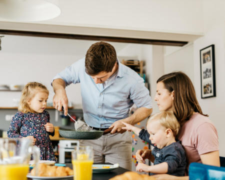 Father serving breakfast to family