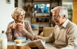 Happy senior woman drinking coffee and talking to her husband during breakfast.
