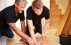 Two men laying wood panel flooring in a house