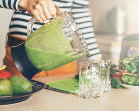 woman's hand pouring green smoothie into a glass