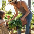 Mother and daughter with fresh vegetable in farm